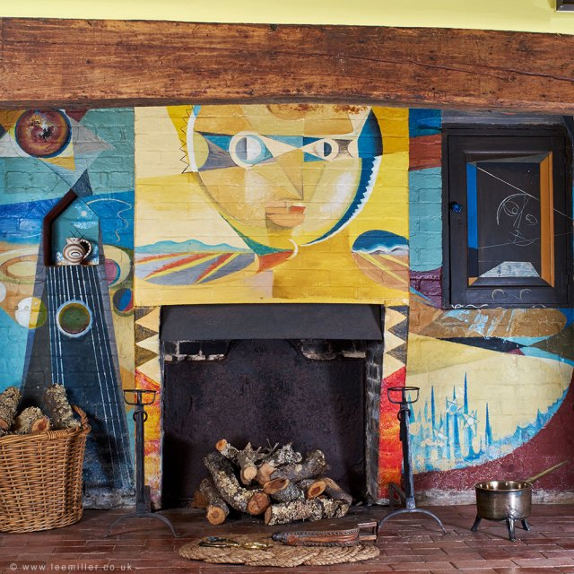 A very colourful painting by Picasso surrounds a fireplace which is filled by logs of wood.