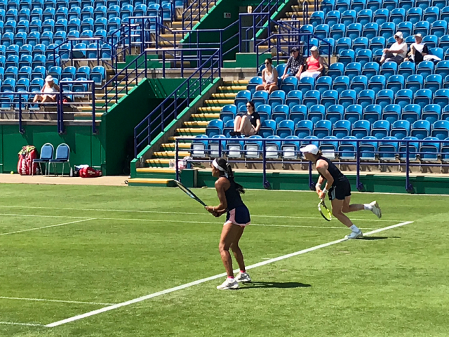 Two women on the tennis court mid game. Behind them, a sparse crowd sits watching the match.