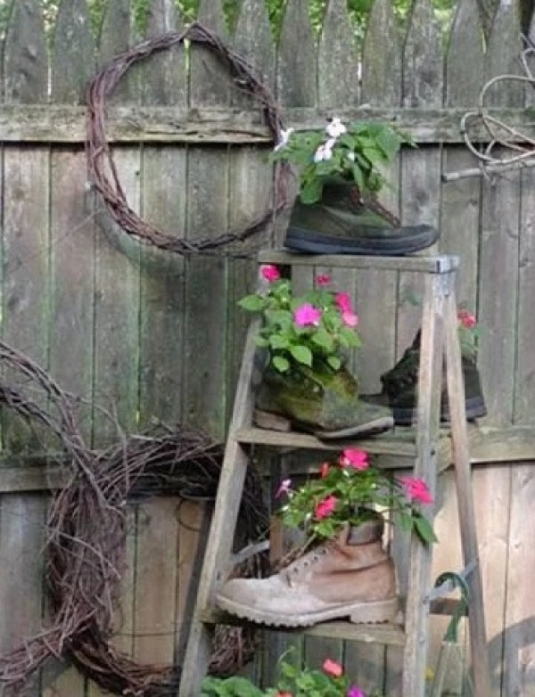 Old boot planters on a small wooden ladder
