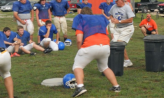 Eagles' head football coach, Mike Rude, demonstrates defensive moves