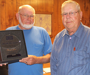 Outgoing councilman Bill Elliot, right, accepts a plaque, recognizing his 28 years serving on the council, from mayor Simmons.