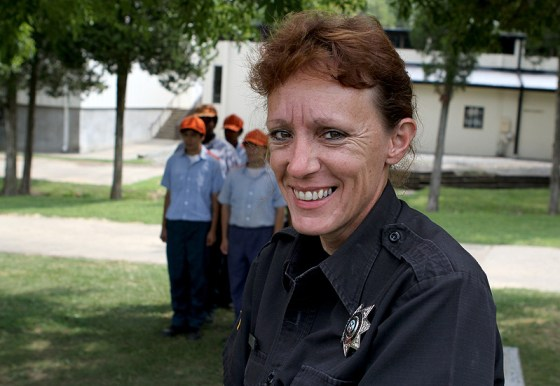 Corrections Officer Penny Poole poses for a portrait with six of her 17 women who have worked in the garden at Dixon Springs Impact Incarceration Program facilities helping to bring fresh produce to the Vienna High School.  Members of the garden crew sometimes spend as much as eight hours a day keeping the garden free of weeds and picking produce.