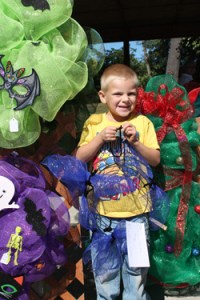 Austin Cole, 4, son of Eric and Amy Cole of Vienna, shows off the mesh wreath he made while helping his mother prepare for Art in the Park.