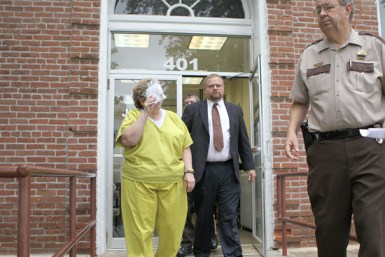 Convicted felon and former Belknap Village clerk Nancy J. Hester (covering face) is escorted out of the Johnson County Courthouse Tuesday afternoon by public defender Jeremy Lloyd and Johnson County Sheriff Elry Faulkner after receiving a sentence of three years for a Class 2 Felony Theft of more than $25,000 from the village she clerked for between 2010 and 2013.