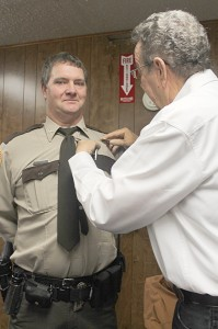 Outgoing sheriff Elry Faulkner pins a sheriff's badge on the chest of Johnson County's new sheriff Charles Harner.