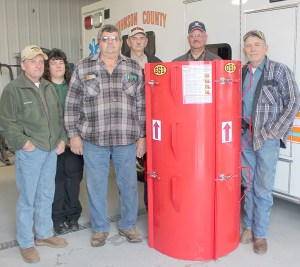 Roger Green, third from left, of Cypress purchased a grain bin rescue tube that he is making available to emergency responders. He turned the piece of life-saving equipment over to the county Thursday morning at the ambulance service. Pictured, from left, are county commissioner Fred Meyer, ambulance service coordinator Wendi Bailey, Roger Green, Johnson County Farm Bureau vice president Glenn Brown, county ESDA coordinator Jim Haney and county commissioner Phil Stewart.