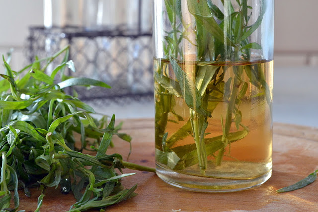 a bottle of diy tarragon vinegar with fresh tarragon sprigs