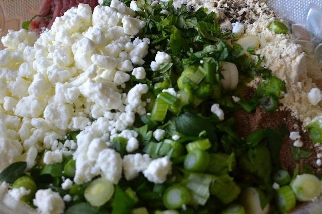 Photo of herbs, onions, cheese, spices, and ground meat in a bowl for Lebanese Meatballs.