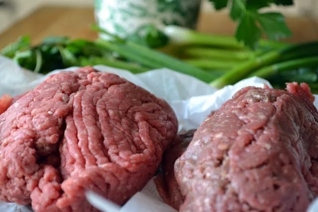 Photo of raw ground meat and spring onions on a table for Lebanese Meatballs.