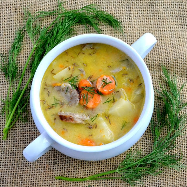 A bowl of cheddar and bratwurst soup with fresh dill