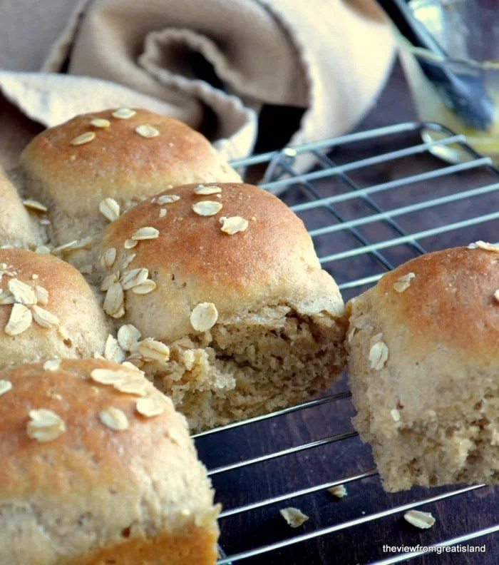 Quick Whole Grain Oat Rolls on a cooling rack with napkin