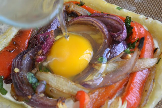 Photo of a raw egg being poured onto an unbaked red pepper and baked egg galette.