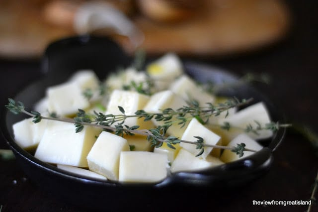 Cheese and thyme in a cast iron dish for baked cheese.