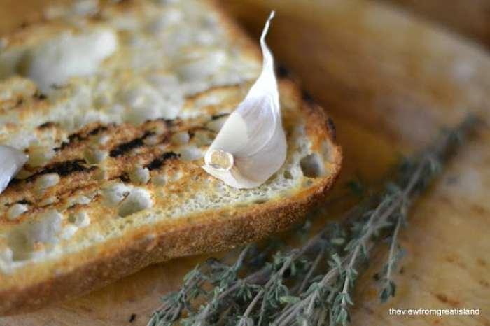 Rubbing toasted bread with fresh garlic clove for mushroom and Gruyere bruschetta
