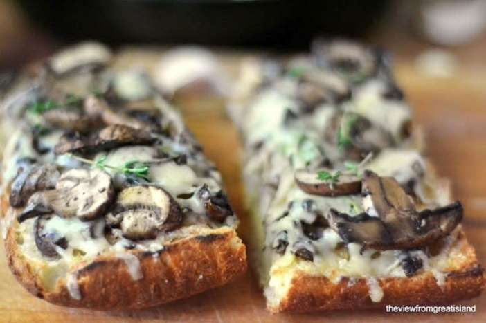two slices of Mushroom and Gruyere Bruschetta on a wooden cutting board