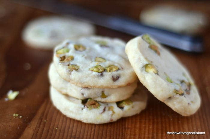 A stack of pistachio shortbread cookies on a wooden table