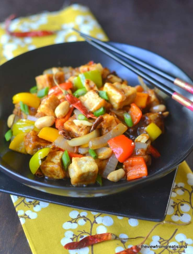 Kung Pao Tofu in a black bowl with chopsticks and floral napkin