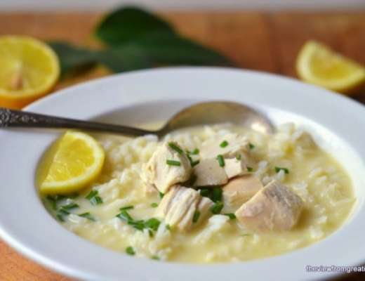 A bowl of Greek Avgolemono Soup with lemons and a spoon