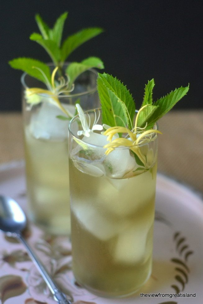 Photo of two glasses of Honeysuckle Iced Tea garnished with mint leaves and honeysuckle blossoms on a tray.