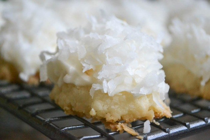 Close up photo of a coconut snowball melting moment on a baking rack.
