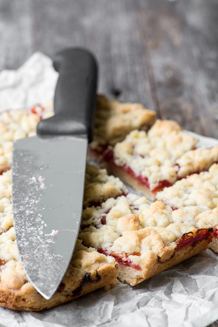 Blood Orange Shortbread Crumble Bars with a knife on parchment paper