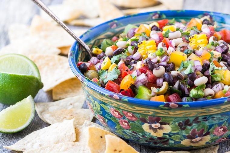Cowboy Caviar in a bowl with chips and lime