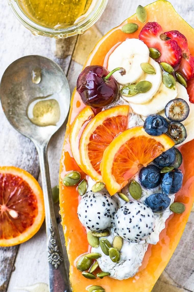 Papaya Breakfast Boats with spoon and honey