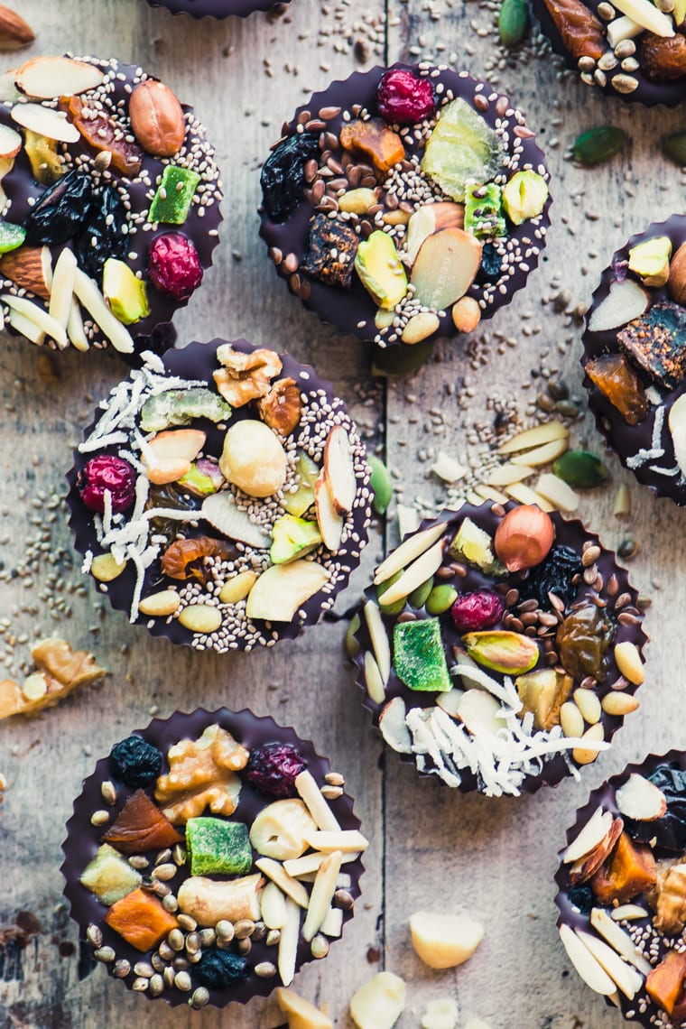 Detox Dark Chocolate Almond Butter Cups topped with dried fruits, nuts, and seeds on a wooden table