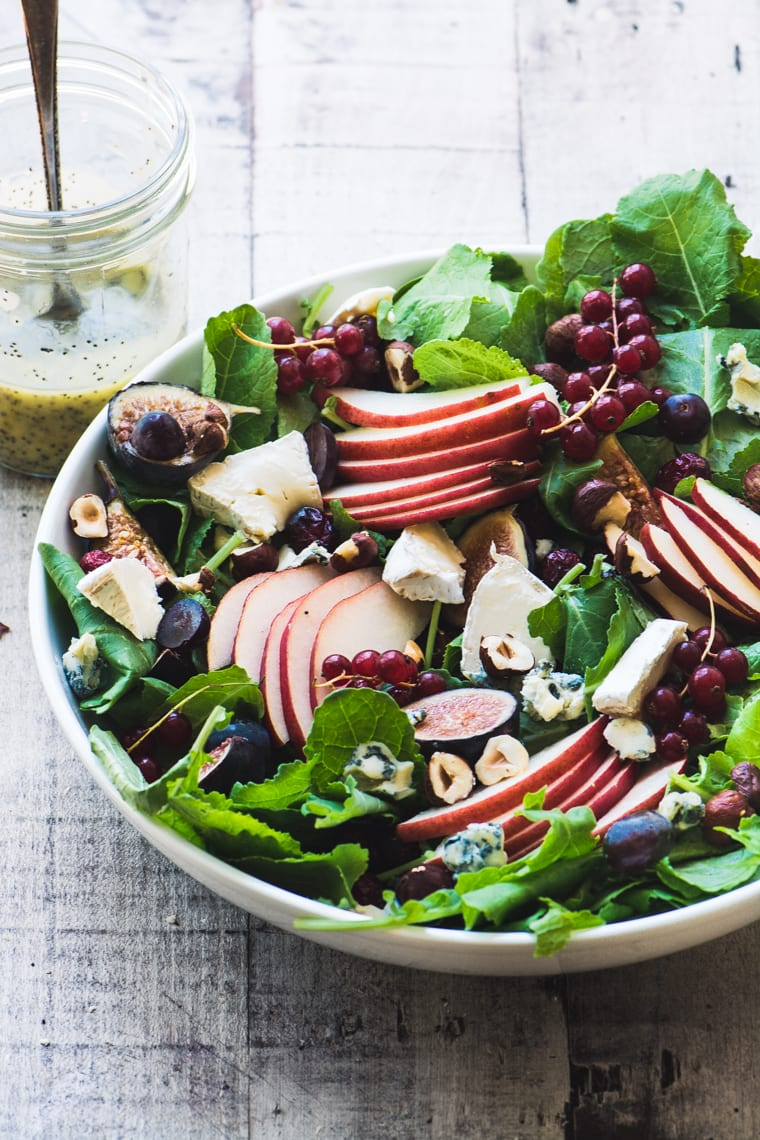 Kale and Fall Fruit Salad with Cider Poppy Seed Dressing on a wooden table
