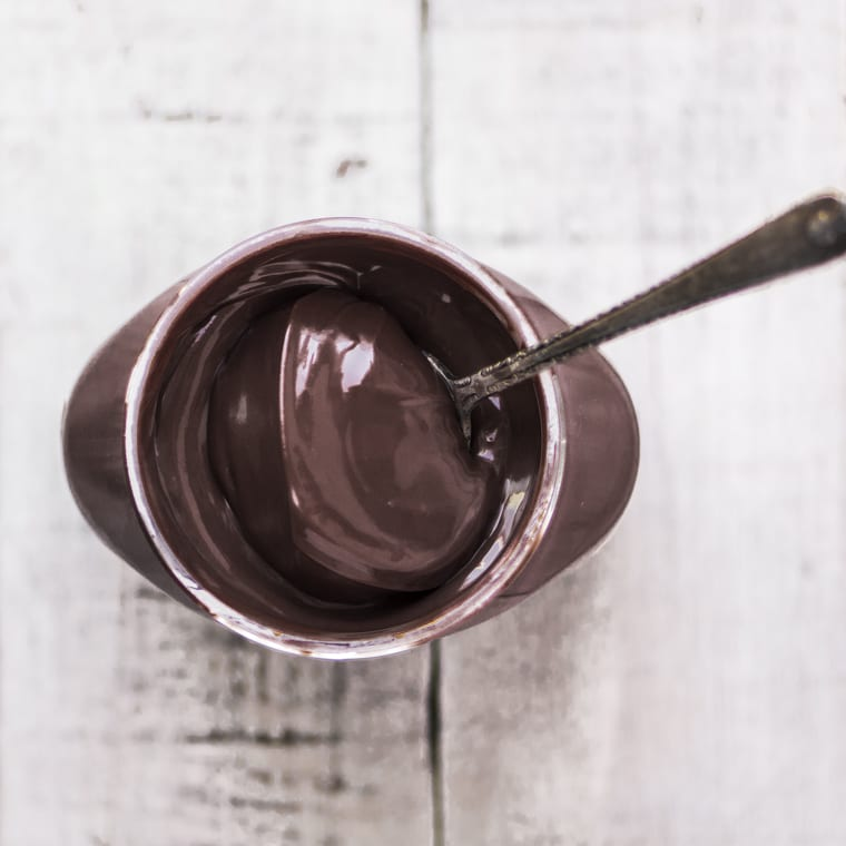 A jar of Nutella with a spoon, ready to make Homemade Nutella Liqueur