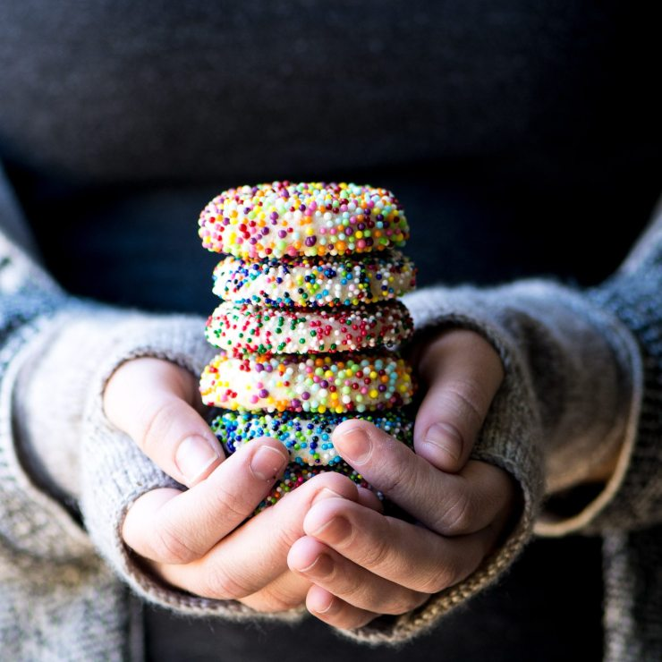 hands holding a colorful stack of sprinkle sugar cookies