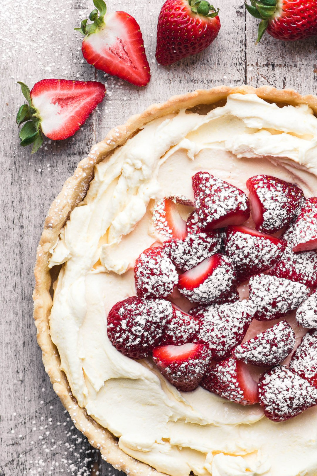 strawberries and cream tart on a wooden board surrounded by fresh strawberries