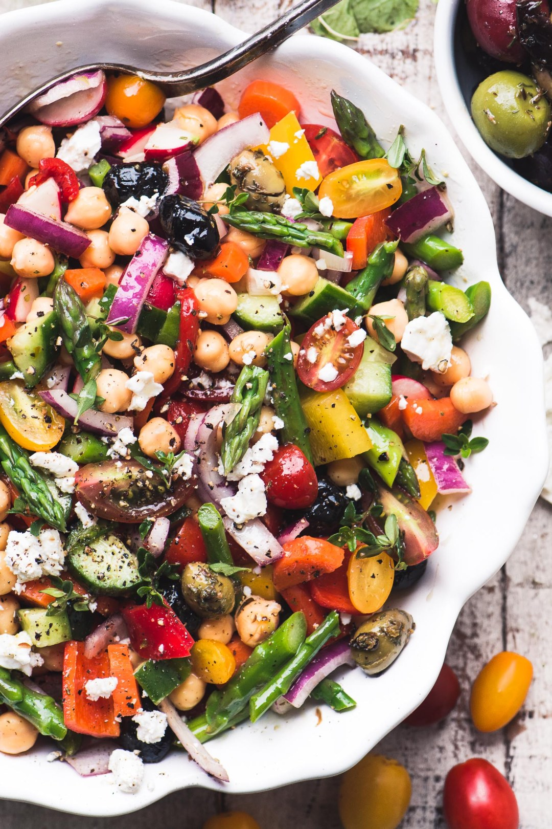 A colorful and healthy Chopped Asparagus Salad on a wooden table with spoon