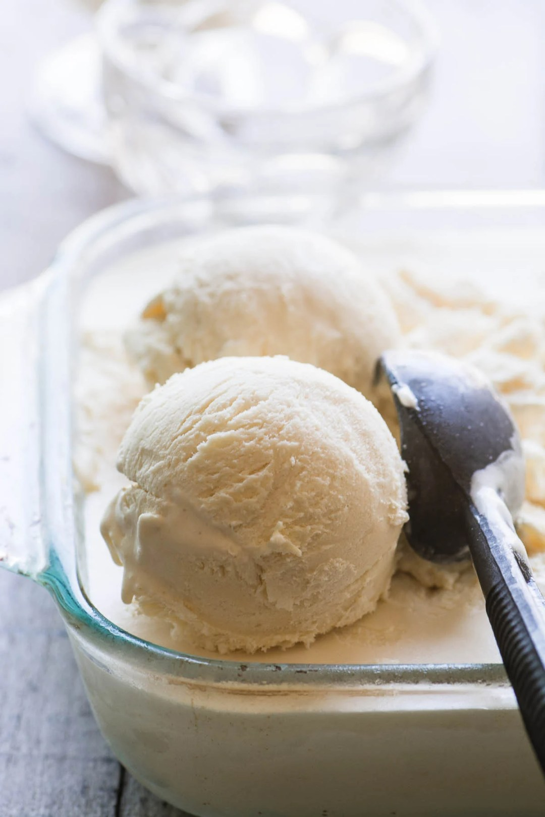 Scoops of Ballymaloe no churn vanilla ice cream with vintage ice cream scoop in glass container
