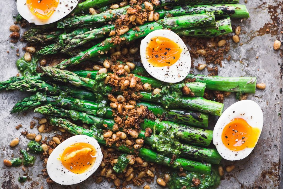 roasted asparagus on a baking sheet with soft boiled eggs