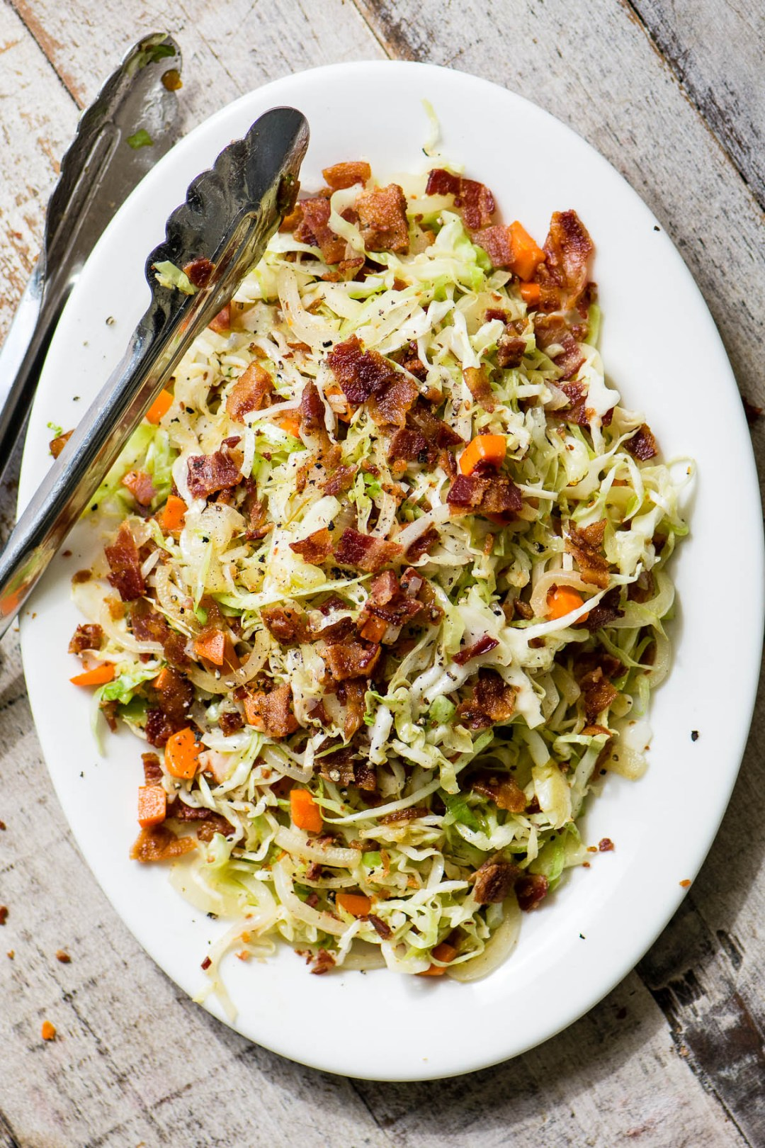 a white platter of fried cabbage and bacon slaw, with metal tongs