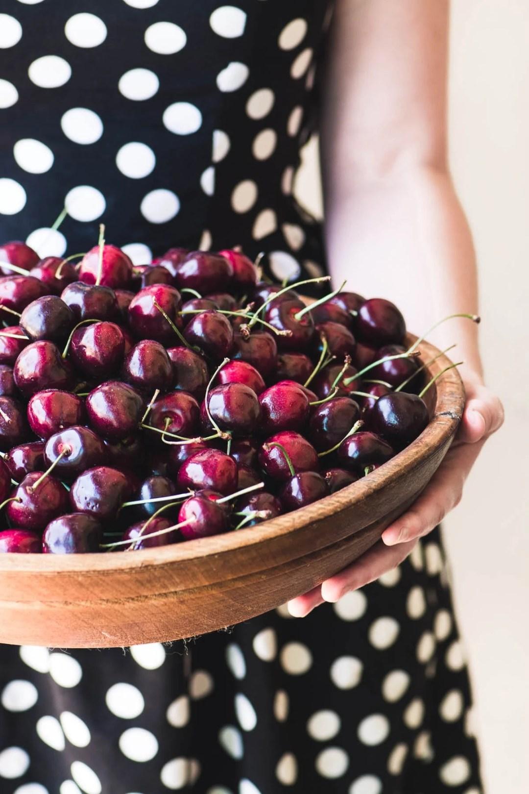 Girl in a polka dot dress holding a bowl of fresh cherries
