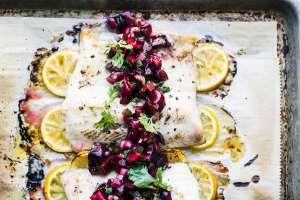 Broiled Whitefish with Cherry Salsa and lemons on a baking sheet