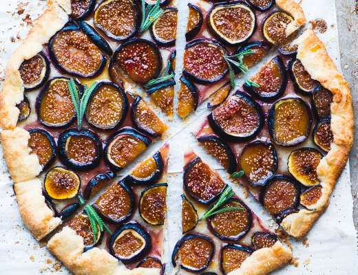 Fig galette with lavender honey sliced into wedges on parchment paper