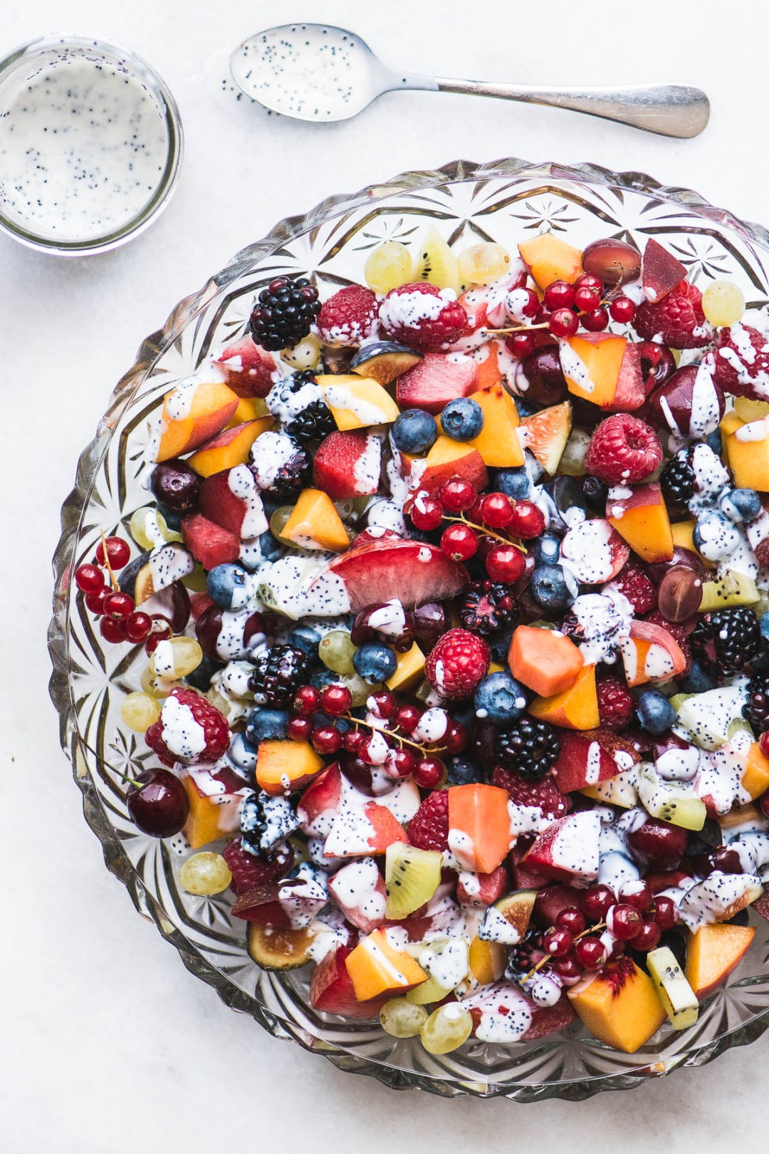a large glass bowl of late summer fruit salad with kefir poppy seed dressing on a marble counter