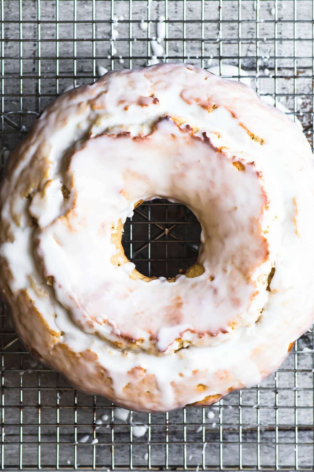 A glazed old fashioned buttermilk doughnut bundt cake on a cooling rack