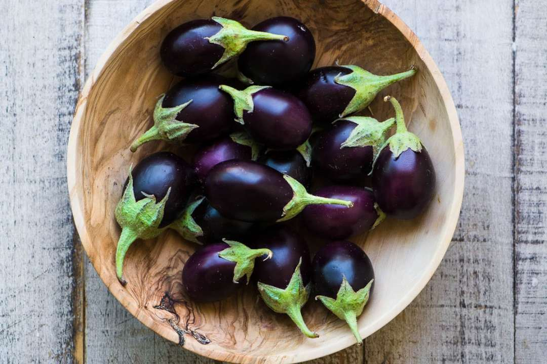 Baby eggplant in a wooden bowl