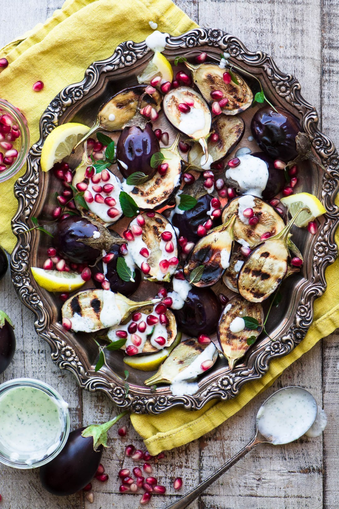 Grilled Baby Eggplant with Minted Yogurt and Pomegranate on a silver platter with yellow napkin