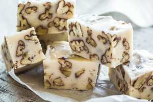 Pieces of Buttermilk Pecan Fudge stacked on parchment paper