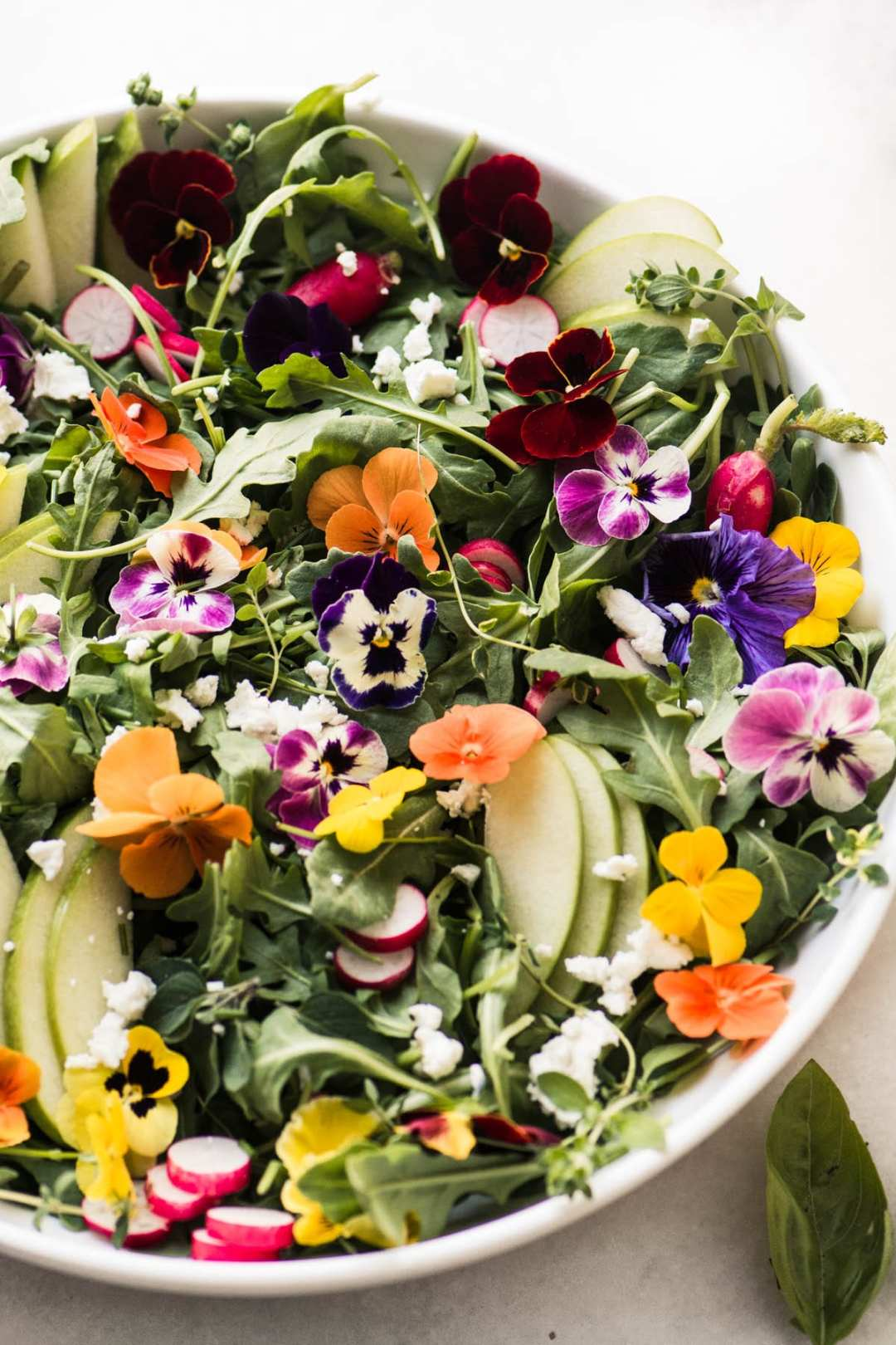Winter pansy salad in a white bowl