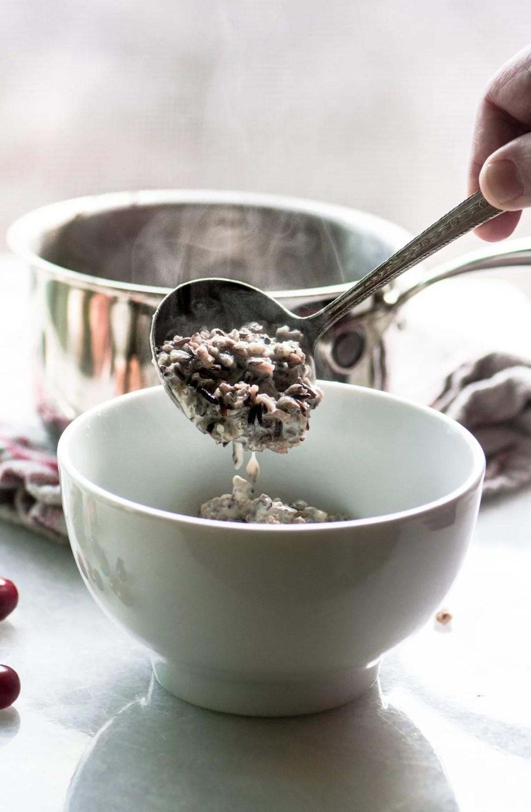 Ladling wild rice porridge into a white bowl