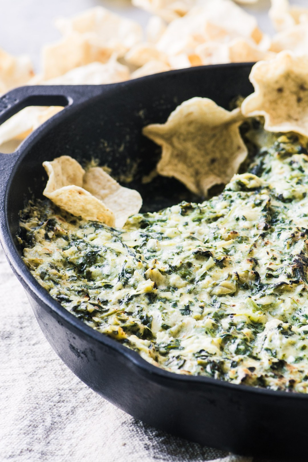 Smokey Spinach Artichoke Dip baked in a cast iron skillet with chips