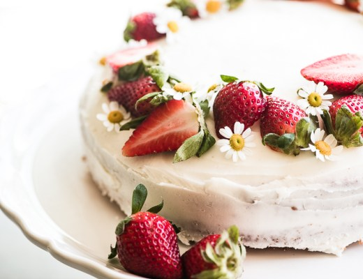 Fresh strawberry cake topped with strawberries and flowers