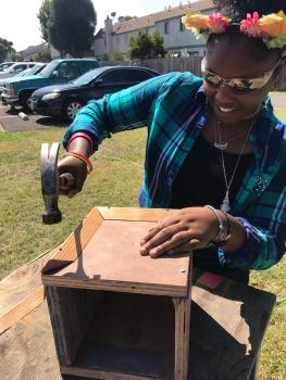 Young woman using hammer to make a box