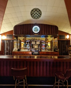an old fashioned bar with mirrored wall behind it